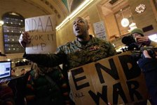 Iraq War veteran Sgt. Shamar Thomas leads a demonstration in New York's Grand Central Station to call attention to a law signed by President Barack Obama that granted extraordinary powers to the military.
